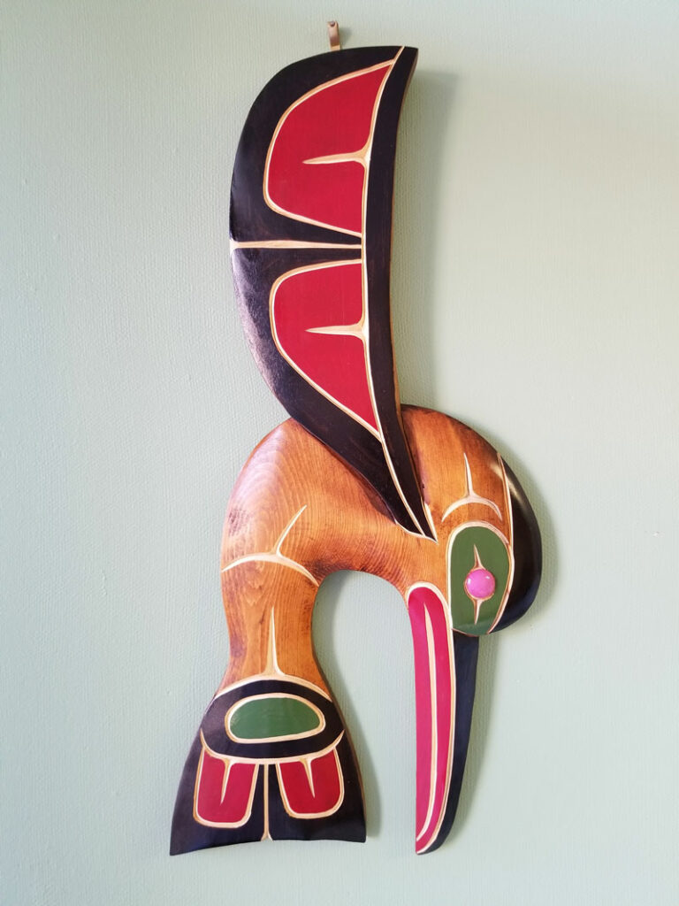 John Patrick Spence carving of a hummingbird, carving, hanging on a wall, in green, red, black and natural wood colours