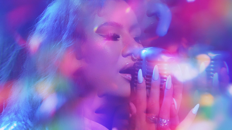 Picture of Michelle Heyóka taken in 2021, singing into a microphone with purple, blue and pink colour filter